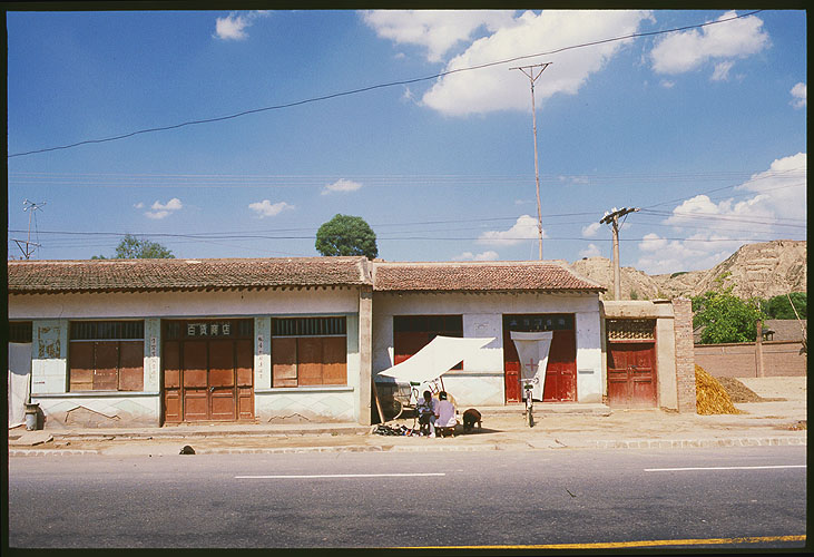 Dwellings and shops along the road<br>A Strip Village: Linxia to Lanzhou, Gansu, People's Republic of China : Landscapes; Buildings.