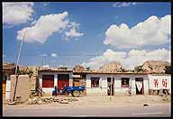 Dwellings and shops along the road :: A Strip Village