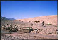 Jiayuguan :: Protecting the Ming Dynasty's Westernmost Extreme :: Emma cycling on the Barbarian side :: of the Ming Great Wall